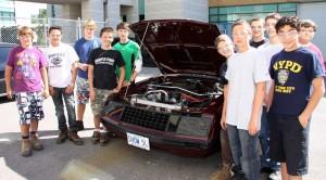 Étudiant devant un auto pendant un stage exploratoire en Techniques des véhicules automobiles