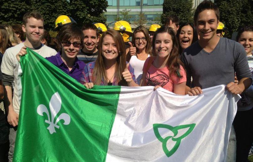Un groupe d'étudiant tenant un drapeau franco ontarien dans la cours centrale de La Cité collégiale