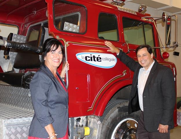 Mme Lise Bourgeois et l'honorable Brad Duguid, devant un camion de pompier