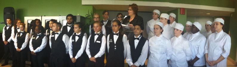 Une vingtaines d'étudiants en gestion culinaire et service hôtelier debout devant, entourant la directrice de l'institut de l'hôtellerie de la gastronomie et du tourisme Lyne Michaud.