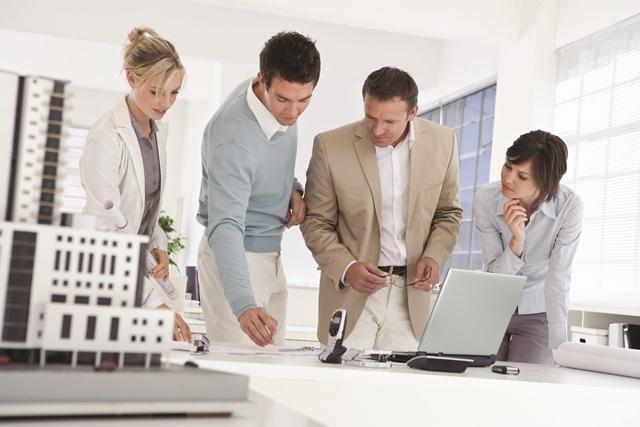 Un groupe de 4 personnes discutent devant un plan d'architecture