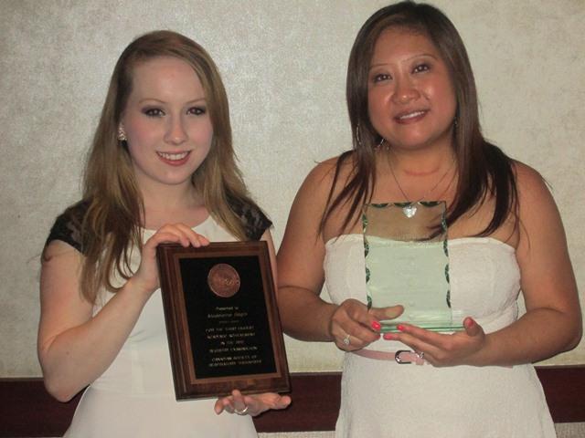 deux étudiantes tenant chacune une plaquette lors de la remise de leur bourses d'études