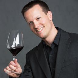Par : Tom Vigeant, Sommelier Coordonnateur du certificat de sommelier tenant une coupe de vin rouge