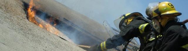 Deux pompiers montés sur une échelle dégagent une fenêtre d'un immeuble en feu.