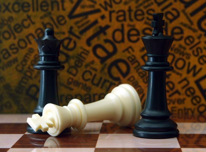 trois pions d'échec sur une table. 2 pions noirs debout et un pion blanc couché.