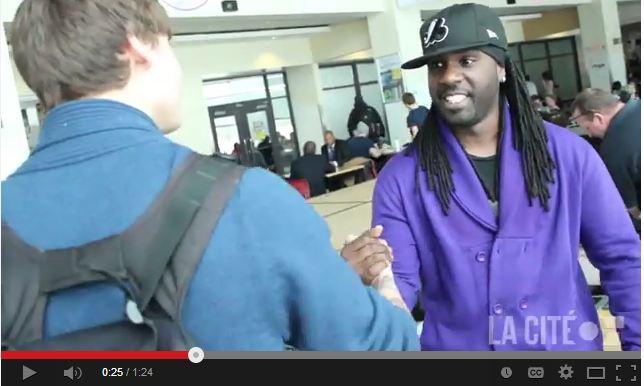 Artiste FLO donne la main à un étudiant sur le campus de la cité