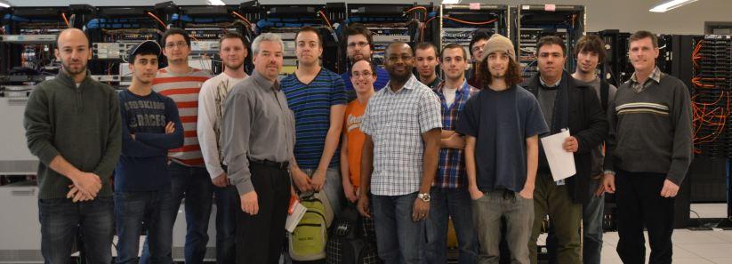 Un groupe de dix étudiants en Technologie de l'information – sécurité informatique posent dans une salle de serveur avec chef technologique de las compagnie Avaya