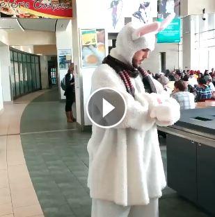 Un jeune homme déguisé en lapin pose dans la cafétériat de La Cité