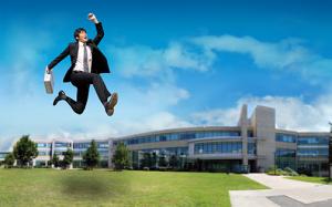 Un jeune professionnel saute dans les airs en célébrant. Les édifices de La Cité sont présentés en arrière plan.