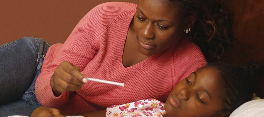 Femme qui prend la température de sa petite fille