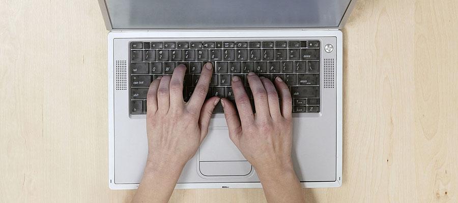 mains sur le clavier d'un ordinateur portable