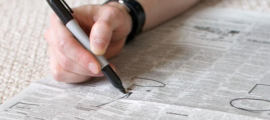 main qui entoure une petite annonce avec un stylo