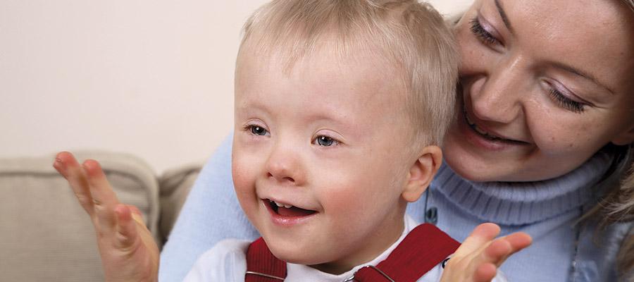 Une intervenante tient sur ses genoux un bambin ayant la trisomie 21.