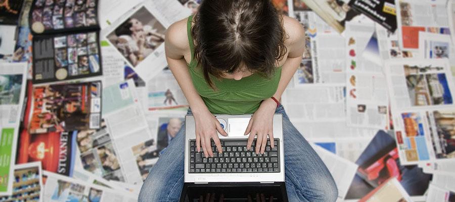 femme assise au milieu de magazines