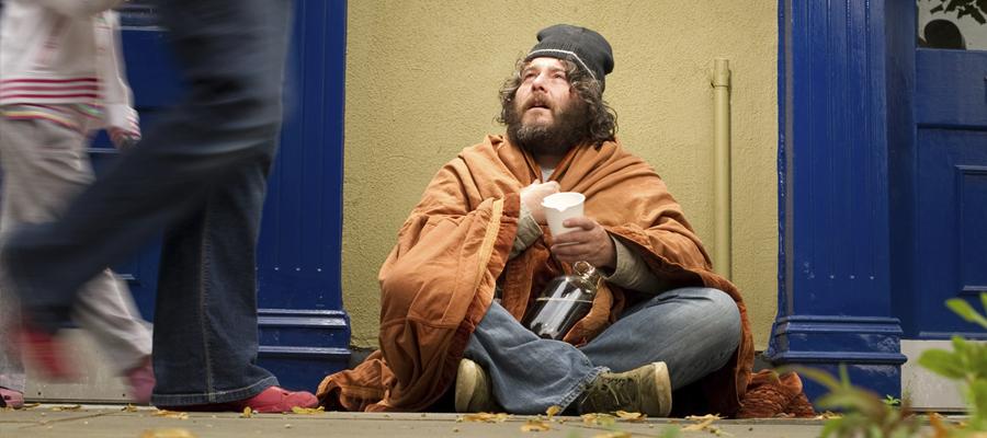 Un sans-abri sur un trottoir passant.