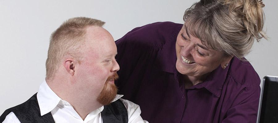 Une dame aide un jeune homme souriant ayant une déficience intellectuelle