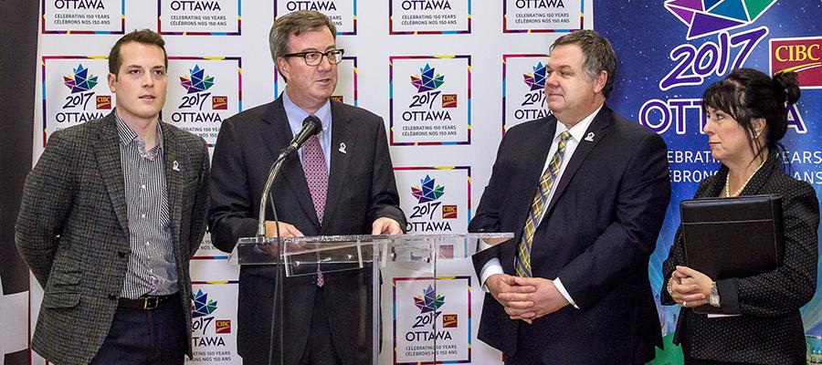 Trois politiciens et la présidente de La Cité devant un podium