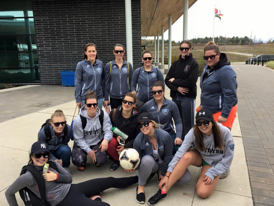 Un groupe de filles devant une école tenants un ballon de soccer