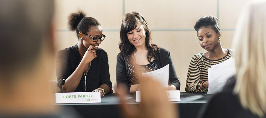 Trois étudiantes participent à une conférence de presse.