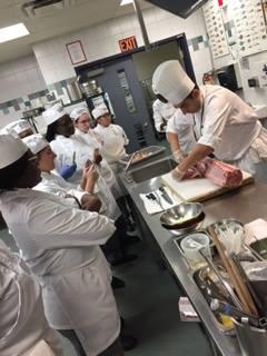 un groupe d'étudiants regarde un chef couper un morceaux de viande