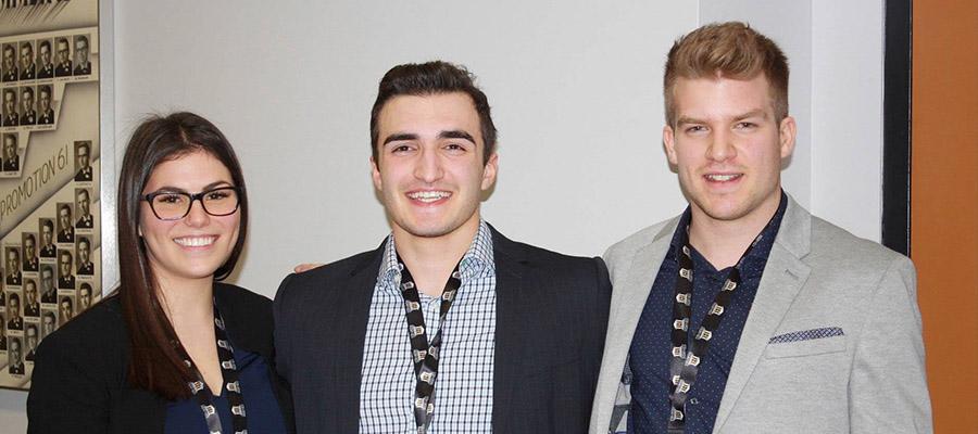 Trois étudiants en administration des affaires posent avec sourire