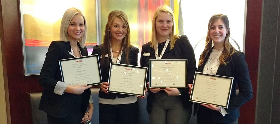 une groupe de quatre étudiante avec un certificat dnas les mains