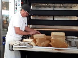 Chef Wayne Murphy retire les pains des moules avant leur vente au kiosque de la Fête du pain.