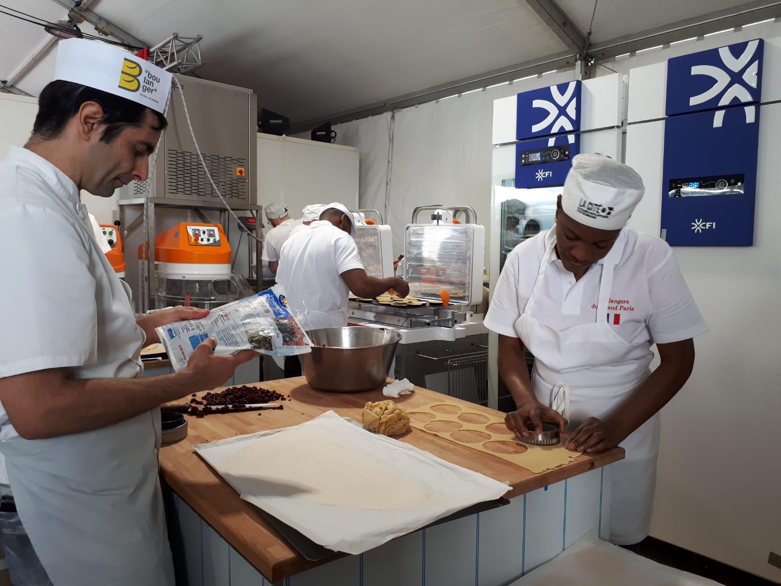 Wendlyne sous le regard d'un boulanger français observant un produit servant à l'une des recettes.